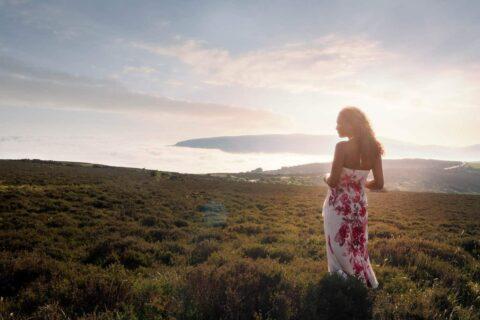 Woman-in-dress-looking-at-sunrise-over-exmoor-devon